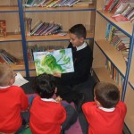 A Y7 student reading to a Y1 class