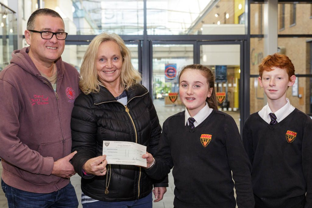 Student hand a cheque over to charity