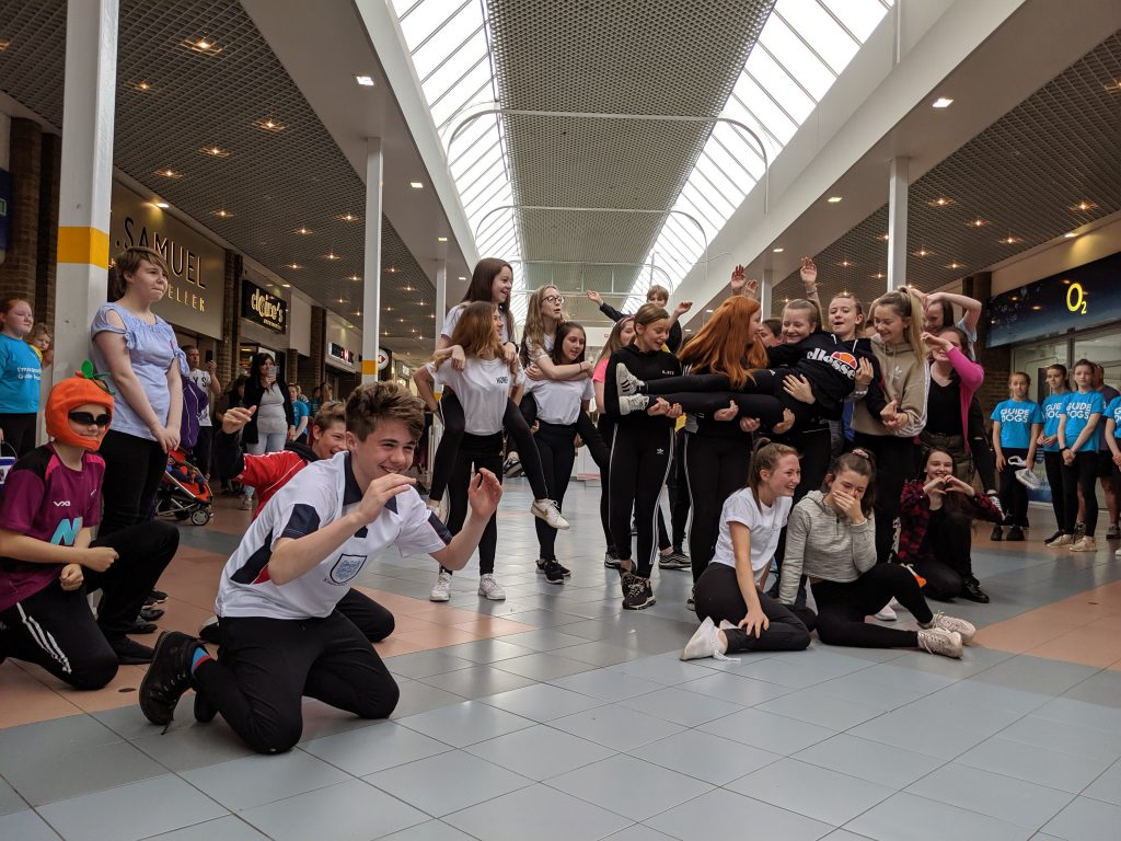 Students performing a dance routine inside a local shopping centre