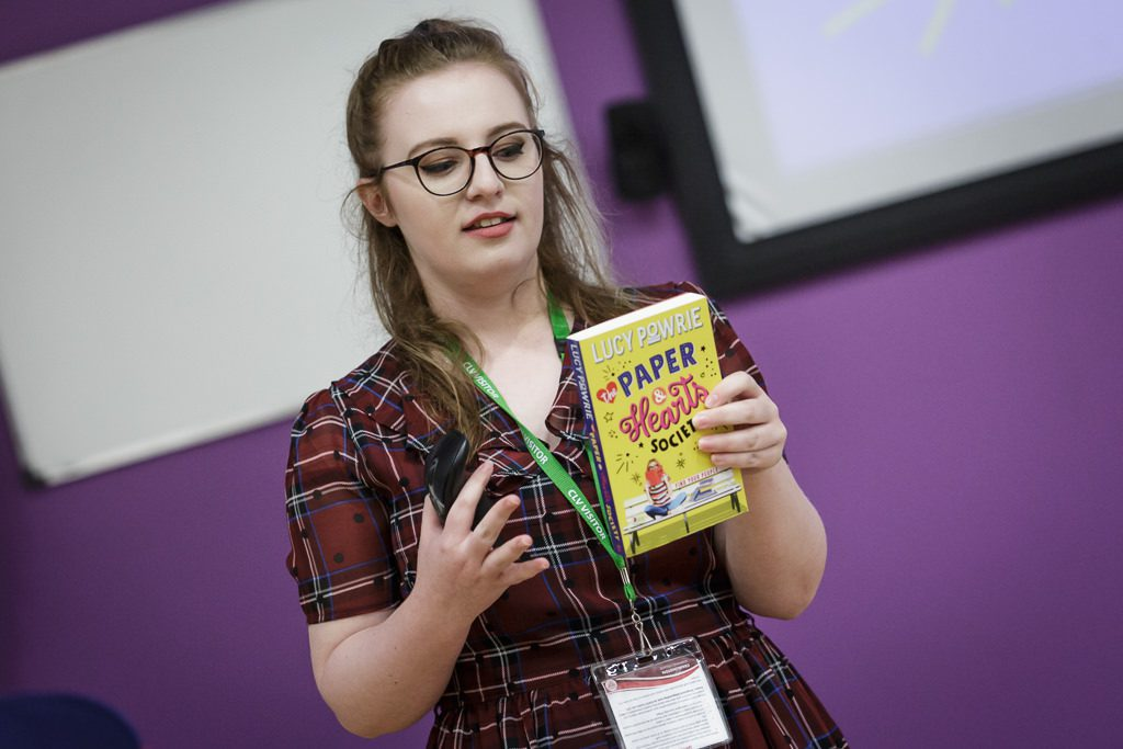 Image of author with her book talking to students