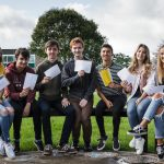 Students sitting on a bench looking happy with their exam results