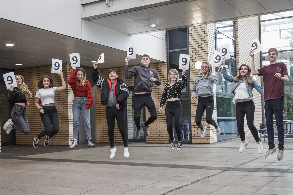 group of students jumping with 9 signs for their exam results