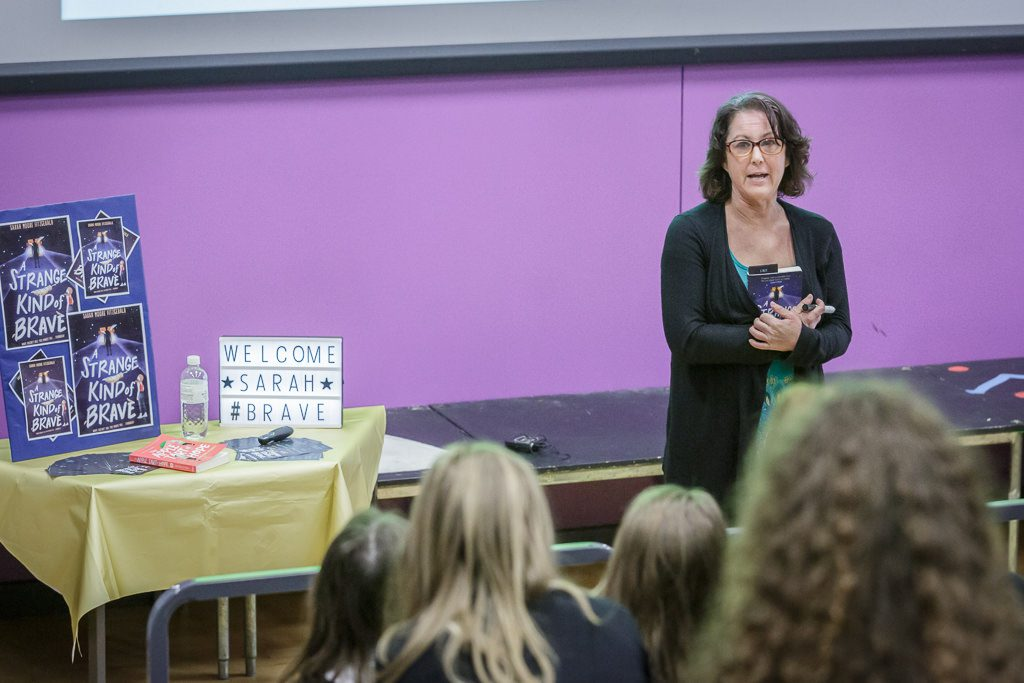 Sarah stands in front of students and talks about her book